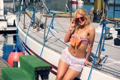 """Blonde Frau im Farbe-two†""""Stückbadeanzug und weiße transparente kurze Hosen auf Yacht Lizenzfreie Stockfotografie"""