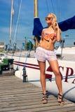 """Blonde Frau im Farbe-two†""""Stückbadeanzug und weiße transparente kurze Hosen auf Yacht Stockfoto"""