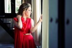 Blonde Frau im Fenster, das ein rotes Kleid trägt Lizenzfreies Stockbild