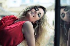 Blonde Frau im Fenster mit rotem Kleid Stockfotografie