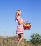 Blonde Frau im Garten mit Äpfeln Lizenzfreies Stockfoto