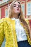 Blonde Frau im gelben Mantel und in der weißen Bluse Lizenzfreies Stockbild