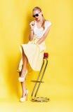 Blonde Frau im gelben Rock mit dem Lutscher, der auf Stuhl sitzt Stockbild