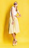 Blonde Frau im gelben Rock und in der rosa Sonnenbrille Stockfoto