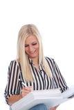 Blonde Frau im gestreiftes Hemd-Schreiben in der Mappe Lizenzfreie Stockfotografie