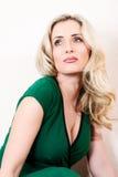 Blonde Frau im grünen Kleid, das auf weißer Vertikale aufwirft Stockfotos