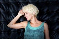 Blonde Frau im grünen Kleid, das vor schwarzem ledernem wa steht Stockfotos