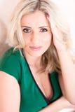 Blonde Frau im grünen Kleid, welches das Loking an der Kamera aufwirft Lizenzfreie Stockfotos