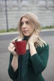 Blonde Frau im grünen trinkenden Spitzenkaffee Lizenzfreies Stockfoto