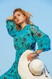 Blonde Frau im Kleid und im Hut gegen Himmel Lizenzfreie Stockfotos