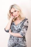 Blonde Frau im Kleid, welches das Schauen auf Kamera aufwirft Stockfotos