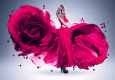 Blonde Frau im langen Rosarosenkleid Stockfotografie