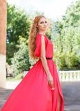 Blonde Frau im langen roten Kleid draußen Lizenzfreie Stockfotografie