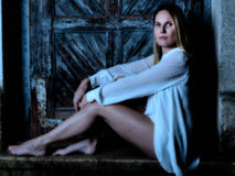 Blonde Frau im Nachtkleid, das im Mondschein sitzt Lizenzfreie Stockfotografie