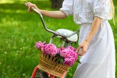 Blonde Frau im Park mit dem Fahrrad, das einen schönen Korb von transportiert Lizenzfreie Stockbilder