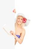Blonde Frau im reisende eine Karte haltenen und aufwerfenden Bikini ist Lizenzfreie Stockfotografie