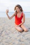 Blonde Frau im roten Bikini am Handy fotografierend Stockbild