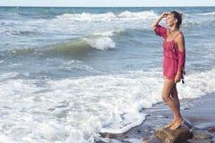 Blonde Frau im roten Kleid, das den Ozean bereitsteht Lizenzfreies Stockbild