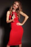 Blonde Frau im roten Kleid, das Glas Champagner hält Lizenzfreies Stockfoto