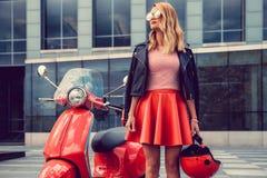 Blonde Frau im roten Rock, der nahe Retro- Roller aufwirft Stockfotos