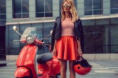 Blonde Frau im roten Rock, der nahe Retro- Roller aufwirft Lizenzfreies Stockfoto