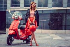 Blonde Frau im roten Rock, der nahe Retro- Roller aufwirft Lizenzfreies Stockbild