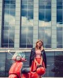 Blonde Frau im roten Rock, der nahe Retro- Roller aufwirft Stockfotografie