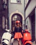 Blonde Frau im roten Rock, der nahe Retro- Roller aufwirft Stockbilder
