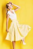 Blonde Frau im schönen gelben Rock Stockfoto