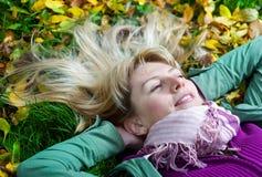 Blonde Frau im Schal, der auf dem Gras liegt Stockfotografie