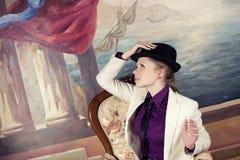 Blonde Frau im schwarzen Hut Stockfotos