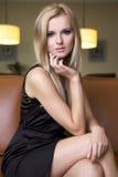 Blonde Frau im schwarzen Kleid Stockfotografie