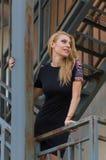 Blonde Frau im schwarzen Kleid auf Treppe Lizenzfreies Stockfoto