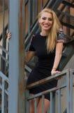 Blonde Frau im schwarzen Kleid auf Treppe Stockbilder