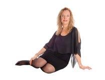 Blonde Frau im schwarzen Kleid, das auf Boden sitzt Stockfoto