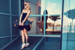 Blonde Frau im schwarzen Kleid, das longboard hält Lizenzfreies Stockfoto