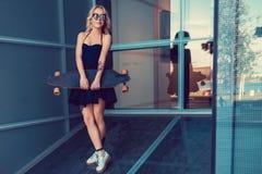 Blonde Frau im schwarzen Kleid, das longboard hält Lizenzfreie Stockfotografie