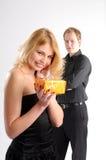 Blonde Frau im schwarzen Kleid mit Geschenk Stockfoto