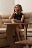 Blonde Frau im schwarzen Kleideraufruf am Handy Stockbild