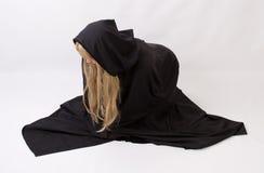 Blonde Frau im schwarzen mit Kapuze Mantel Stockfotos