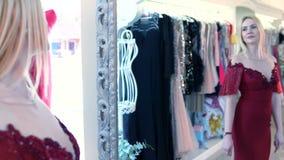 Blonde Frau im sexy roten Abendkleid überschreitet entlang den Shop Reflexion im Spiegel stock video