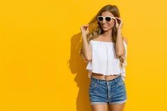 Blonde Frau im Sonnenlicht gegen gelbe Wand Stockfoto