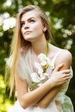 Blonde Frau im Weiß unter grünen Bäumen Lizenzfreie Stockbilder