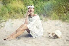 Blonde Frau im weißen Kleid, das auf dem Strand sitzt Stockfotografie