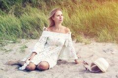 Blonde Frau im weißen Kleid, das auf dem Strand sitzt Stockfoto