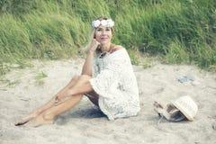 Blonde Frau im weißen Kleid, das auf dem Strand sitzt Stockfotos
