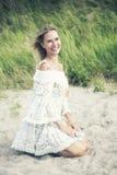 Blonde Frau im weißen Kleid, das auf dem Strand sitzt Lizenzfreies Stockfoto