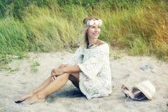 Blonde Frau im weißen Kleid, das auf dem Strand sitzt Lizenzfreie Stockfotografie