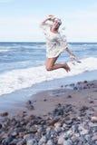 Blonde Frau im weißen Kleid, das auf den Strand springt Stockfotos