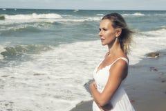 Blonde Frau im weißen Kleid, das den Ozean bereitsteht Stockfoto